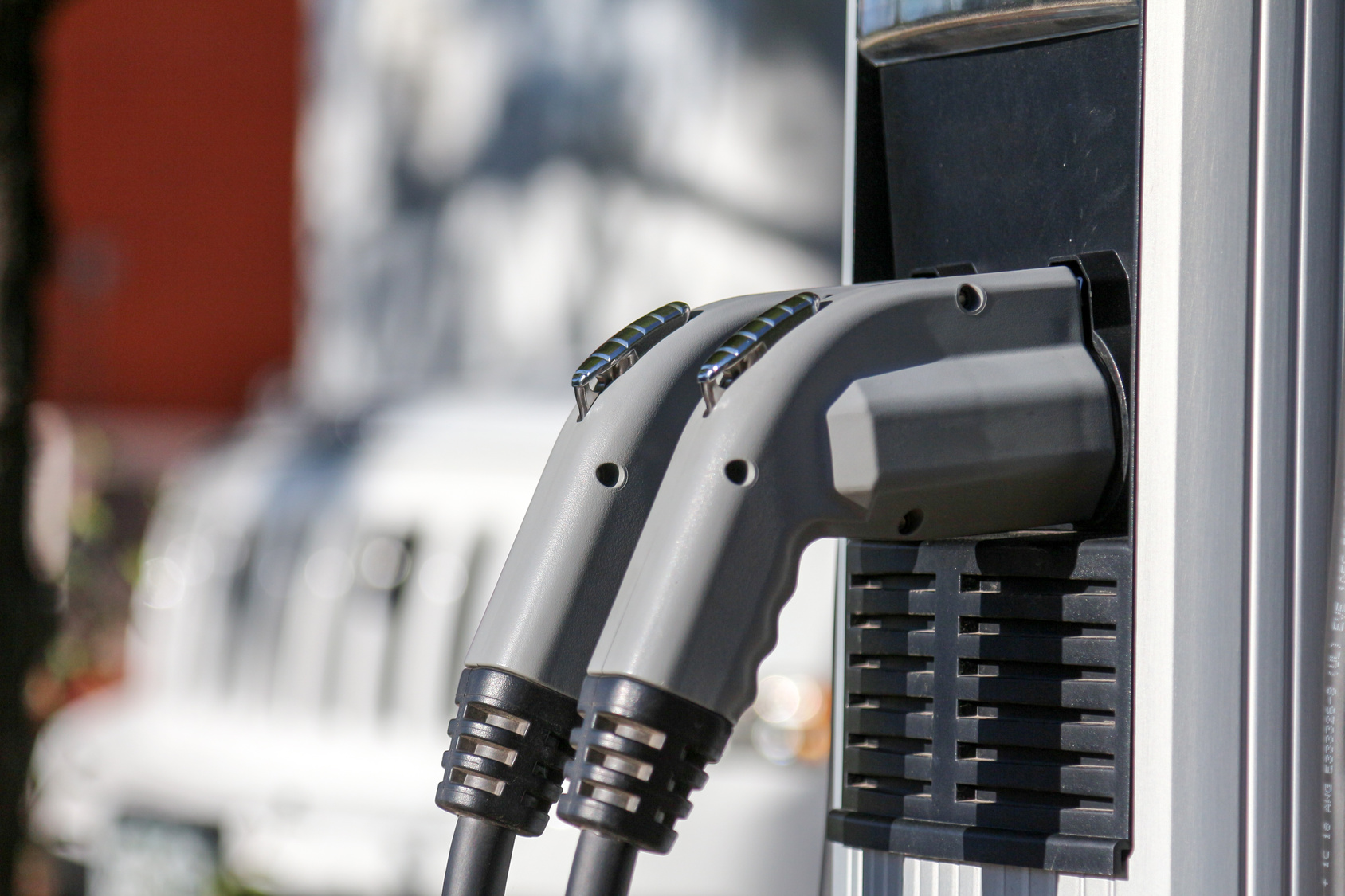 A pair of grey electric car chargers rest comfortably on the charging stations