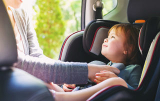 Mother buckling young daughter into car seat